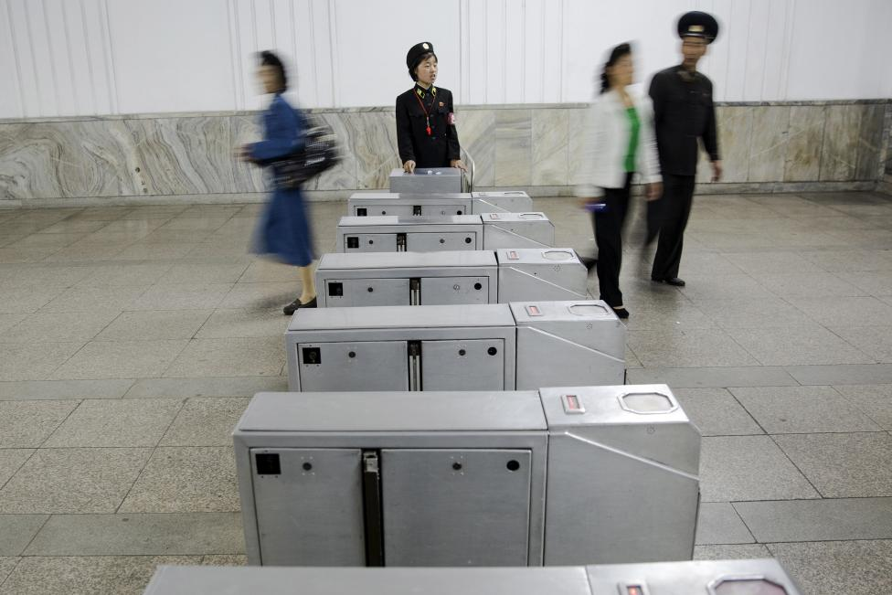 Passengers enter and exit a subway station visited by foreign reporters during a government organised tour in Pyongyang