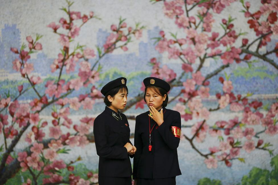 Two railway workers chat in front of a flower mural inside a subway station visited by foreign reporters during a government organised tour in Pyongyang