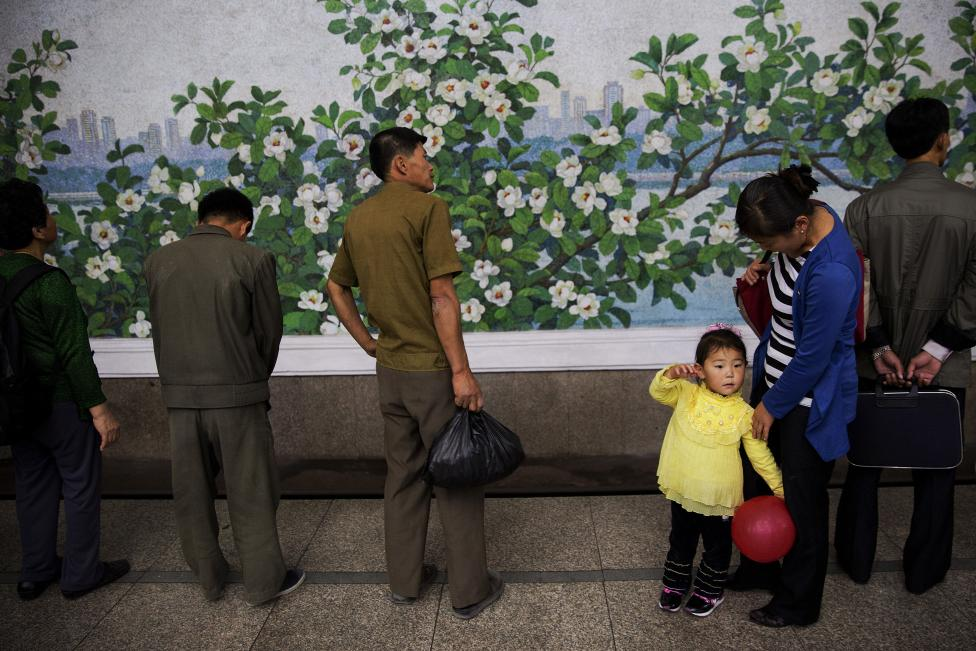 A girl holds a red balloon as she and others wait for a train at a subway station visited by foreign reporters during a government organised tour in Pyongyang