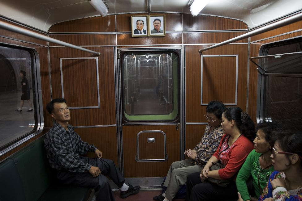 Passengers sit inside a train that stopped at a subway station visited by foreign reporters during a government organised tour in Pyongyang