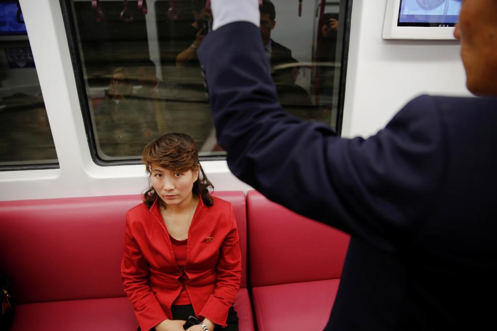 A passenger wearing red travels on a recently introduced new train during a government organised visit to the subway for foreign reporters in Pyongyang