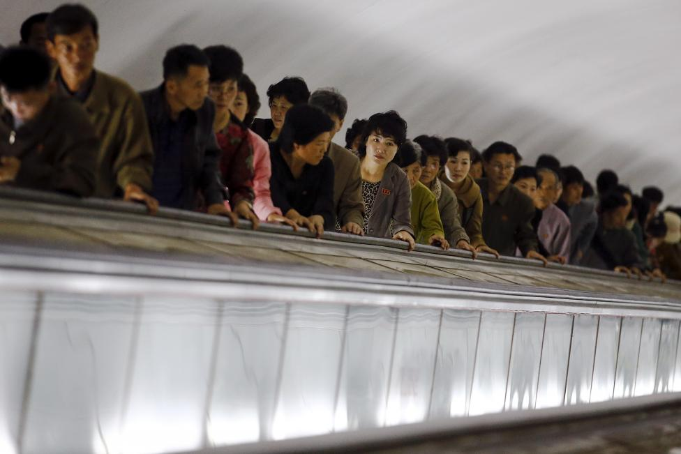 People use escalators to leave a subway station visited by foreign reporters during a government organised tour in Pyongyang