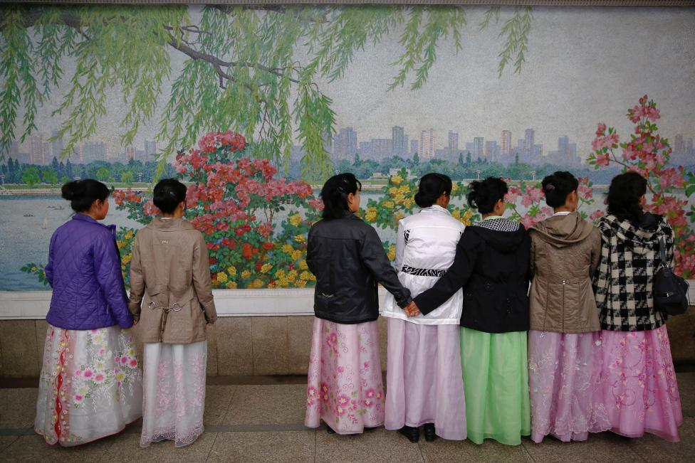 Women wearing traditional clothes wait for the train inside a subway station in central Pyongyang