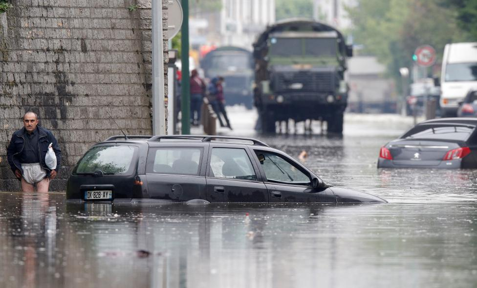 A resident escapes from the flooded area of Villeneuve-Trillage suburb in Villeneuve Saint-Georges
