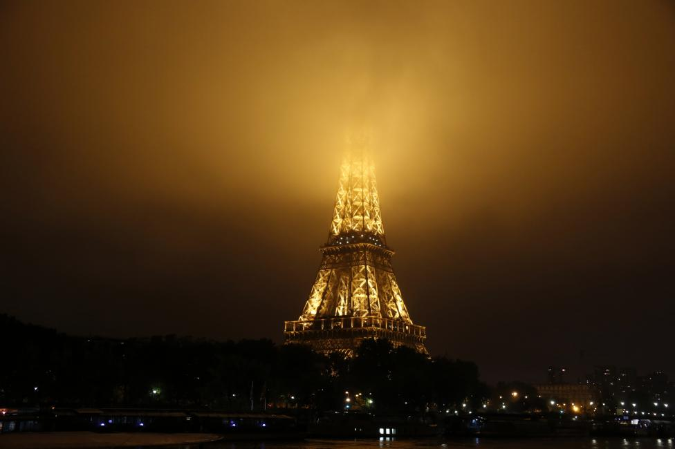 Fog covers the top of the Eiffel Tower as rainy weather continues in Paris