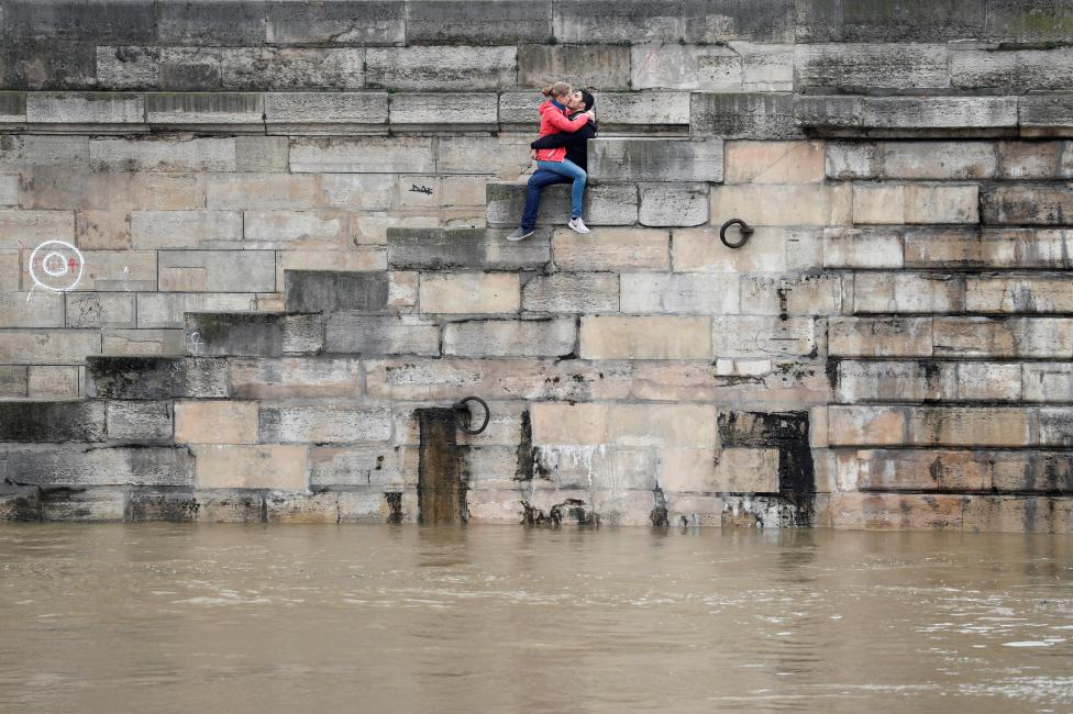 A couple exchanges kisses on the bank as high waters causes flooding along the Seine River in Paris