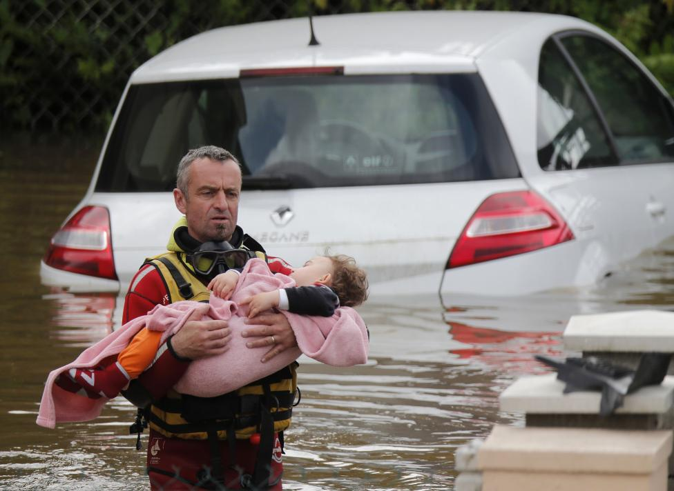 French firefighters evacuates a baby from a flooded area after heavy rain falls in Chalette-sur-Loing
