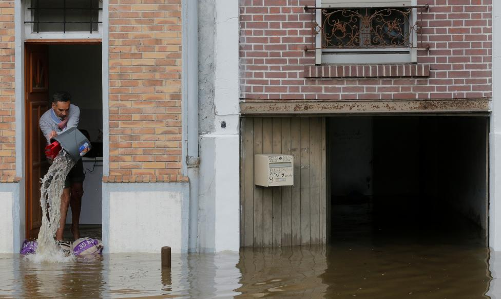 A man scoops water from his house in the flooded suburb of Villeneuve-Trillage in Villeneuve Saint-Georges