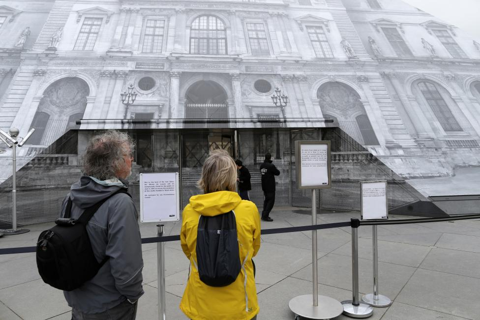 Tourists read information notices that indicate that the Louvre Museum is closed due to the rising Seine River in Paris