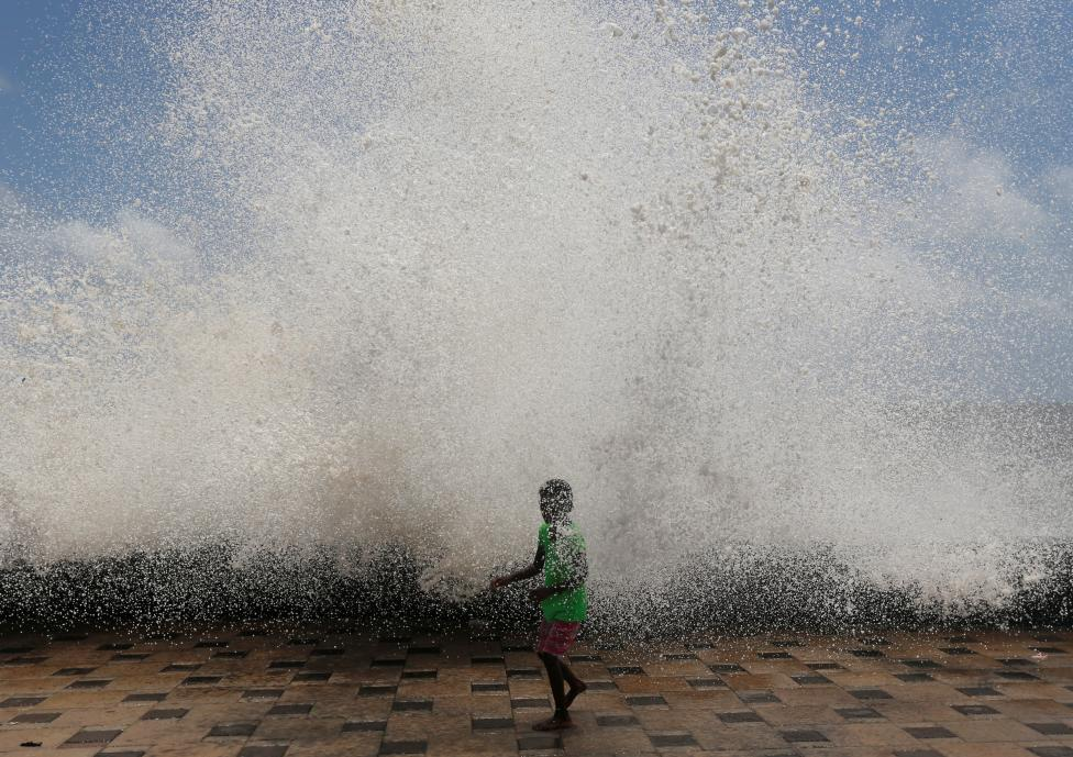 A young girl gets drenched in a large wave during high tide at a sea front in Mumbai