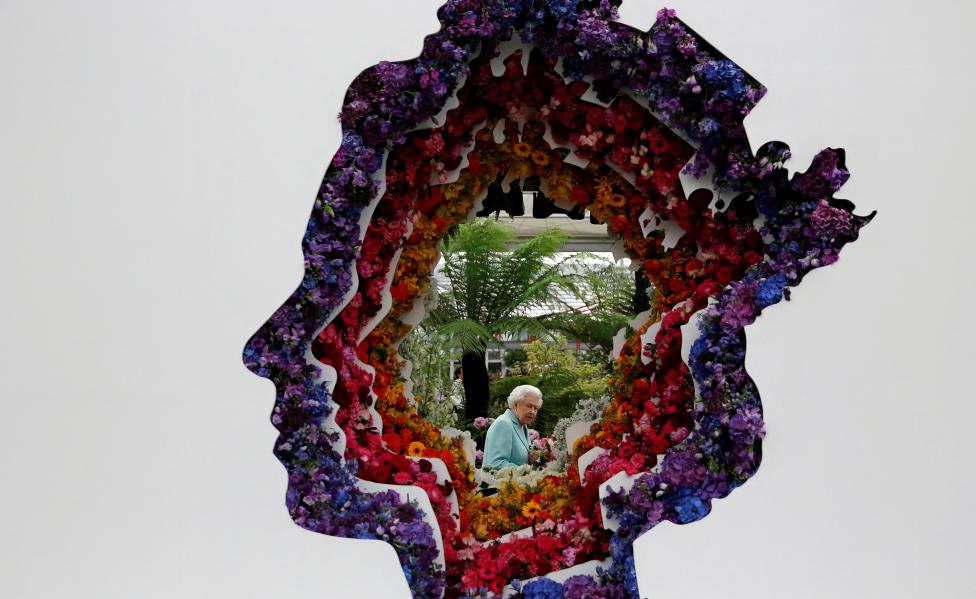 Britain's Queen Elizabeth II is pictured through a gap in a floral exhibit by the New Covent Garden Flower Market, which features an image of the Queen, during a visit to the 2016 Chelsea Flower Show in central London