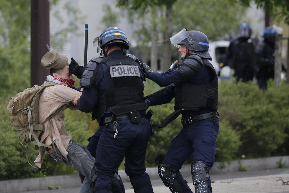 French police apprehend a youth during a demonstration to protest the government's proposed labor law reforms in Nantes
