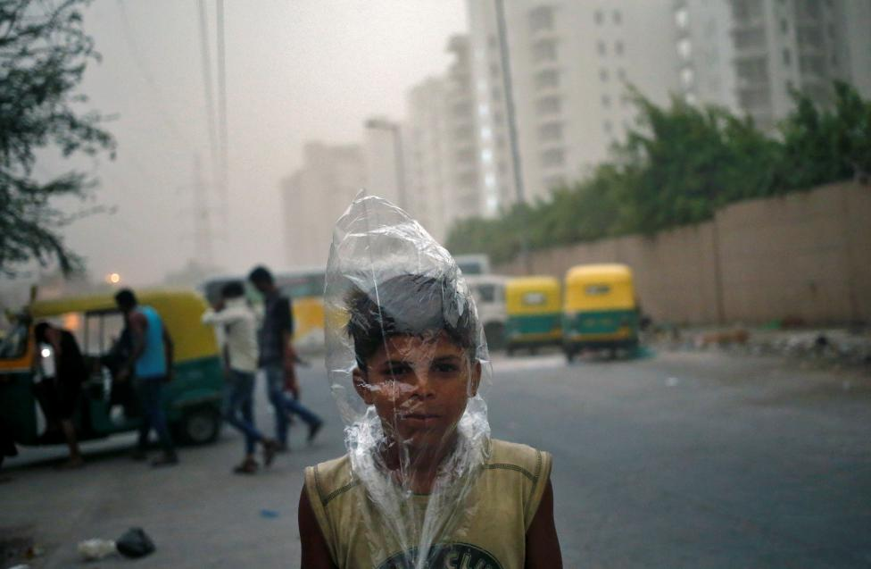 A young boy uses a plastic bag to protect himself from a dust storm in New Delhi