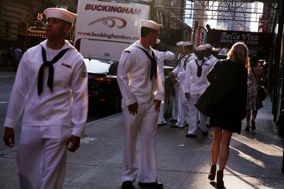 U.S. Navy sailors watch a woman walk past as they walk through Times Square during Fleet Week in New York
