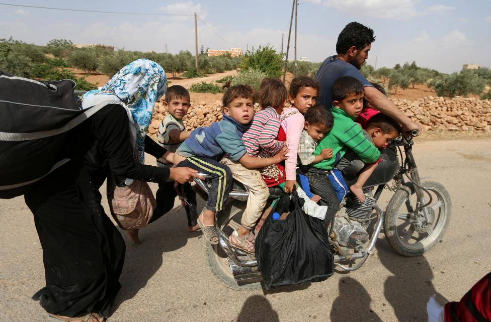 Civilians, who fled the violence in Manbij city, arrive to the southeastern rural area of Manbij, in Aleppo Governorate
