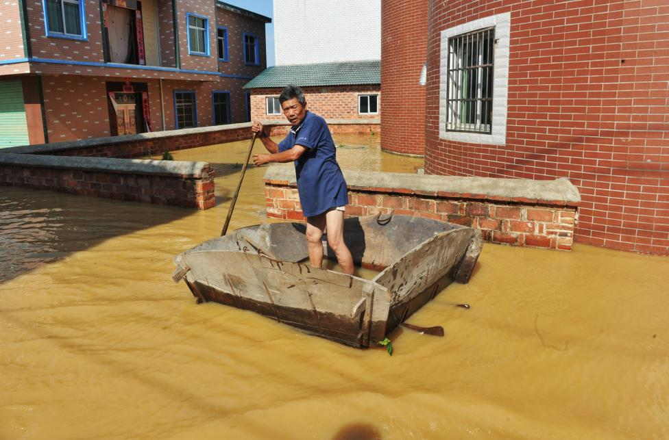 A man rows on a flooded area in Poyang County, Jiangxi province