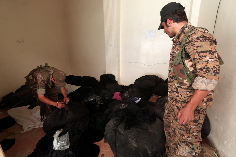Syria Democratic Forces (SDF) fighters inspect bags of niqabs at a centre that was used by Islamic State religious police (al-Hisbah) in Manbij, Aleppo Governorate
