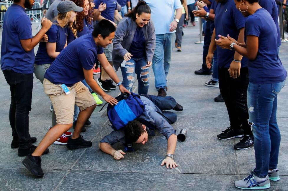 Apple workers assist a customer who fell down before going into the Apple Inc. during the sale of the iPhone 7 smartphone in New York, U.S.