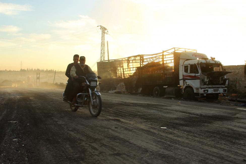 Men drive a motorcycle near a damaged aid truck after an airstrike on the rebel held Urm al-Kubra town