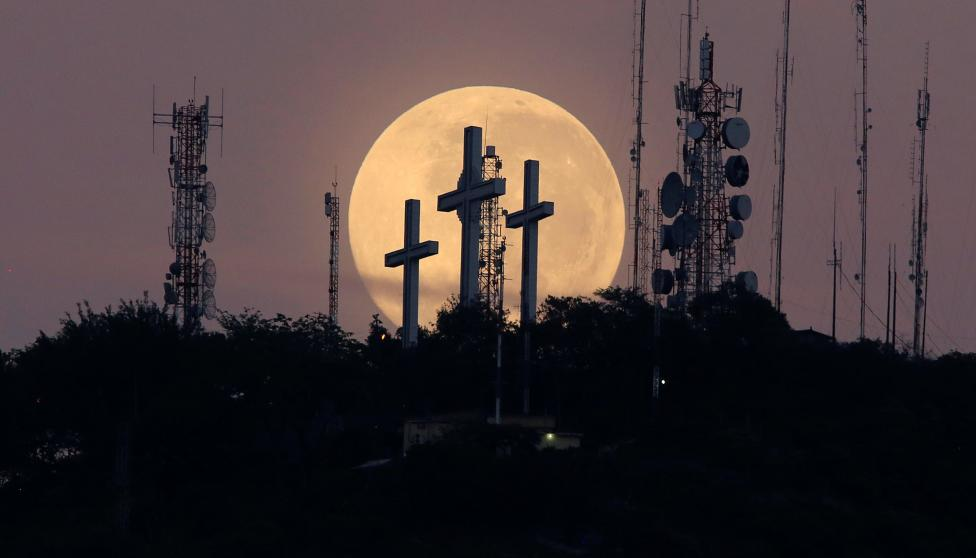 The full moon is seen behind the hill of the three crosses in Cali
