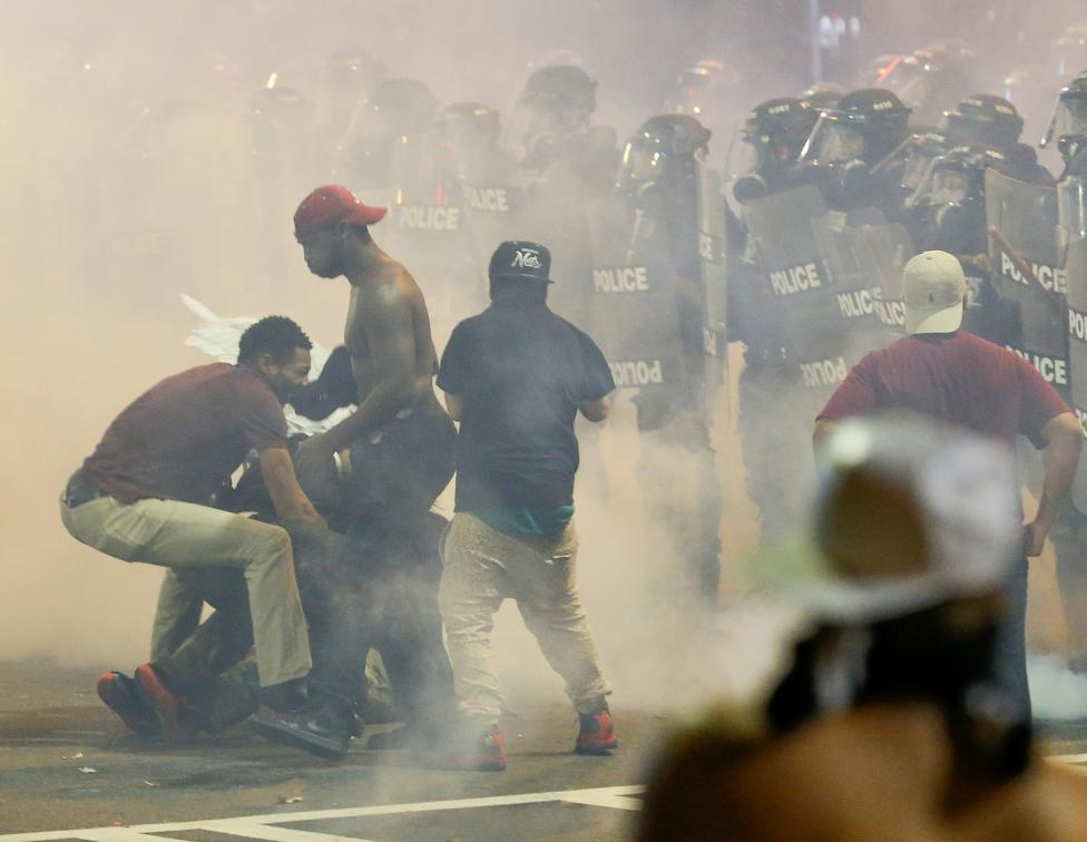 People maneuver amongst tear gas in uptown Charlotte, NC during a protest of the police shooting of Keith Scott, in Charlotte
