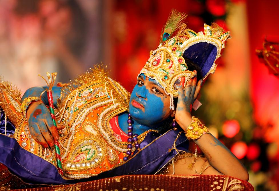 A girl dressed up as Hindu Lord Krishna performs during Janmashtami festival celebrations in Ahmedabad