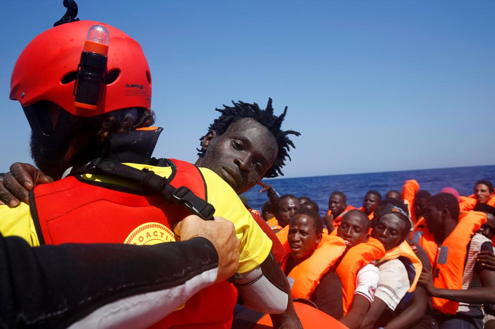 A migrant is carried from an overcrowded dinghy by a member of the Spanish NGO Proactiva during a rescue operation by the Spanish NGO Proactiva, off the Libyan coast in Mediterranean Sea