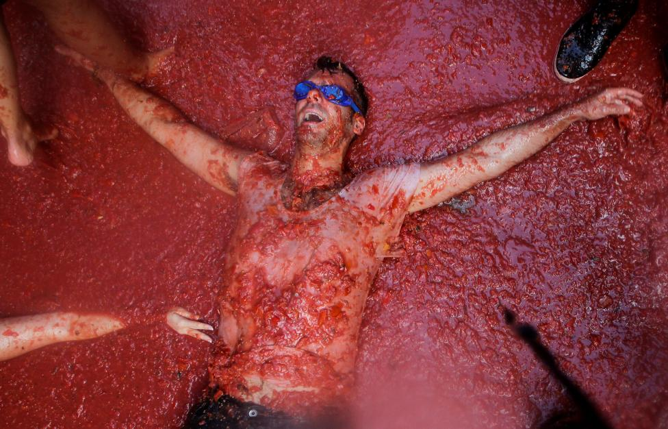 A reveller lies in tomato pulp during the annual Tomatina festival in Bunol near Valencia