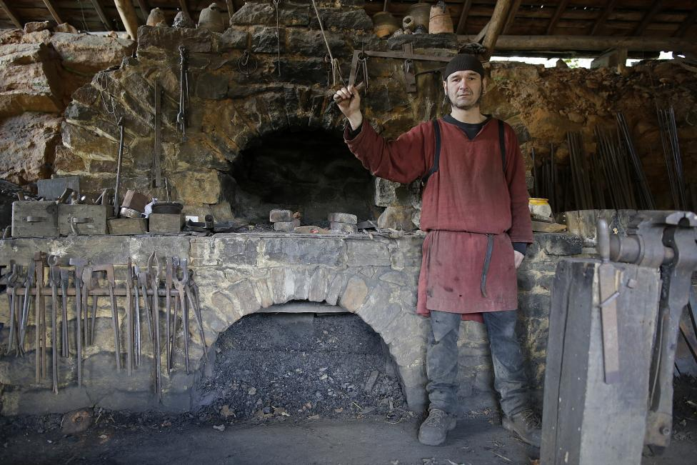 Clement Guerard, blacksmith at the site since 1999, poses in his workshop at the construction site of the Chateau de Guedelon near Treigny
