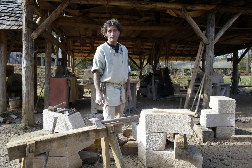 Eugene Kedadra, stonecutter at the site since 1999, poses in his workshop at the construction site of the Chateau de Guedelon near Treigny