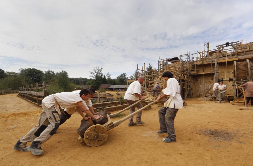 Workers carry stones at the construction site of the Chateau de Guedelon near Treigny