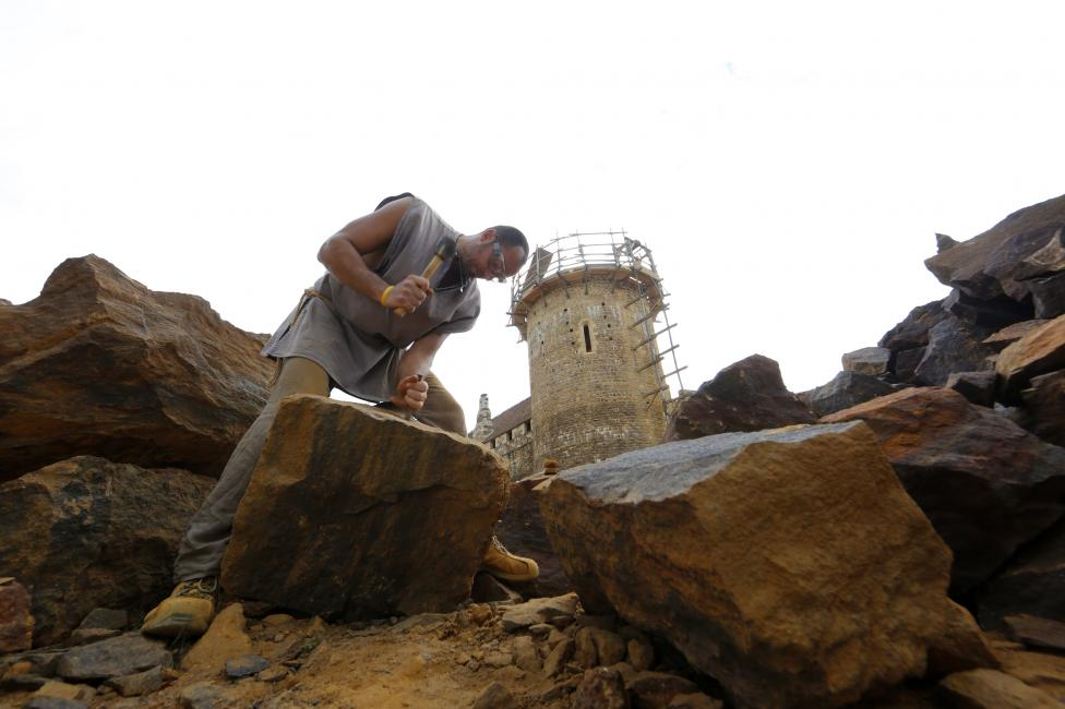 A stonecutter works at the construction site of the Chateau de Guedelon near Treigny