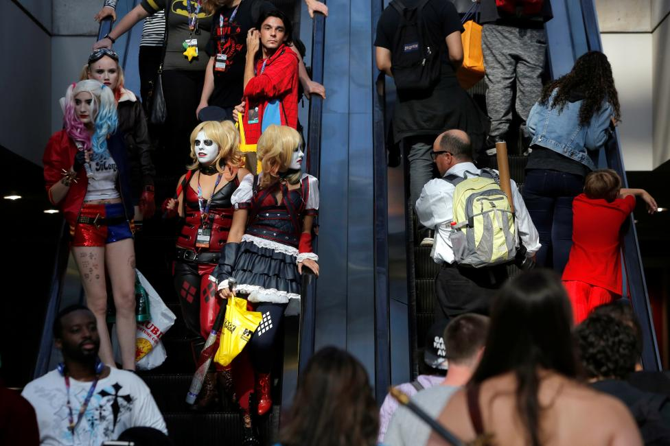 People dressed as Harley Quinn ride an escalator at New York Comic Con in Manhattan