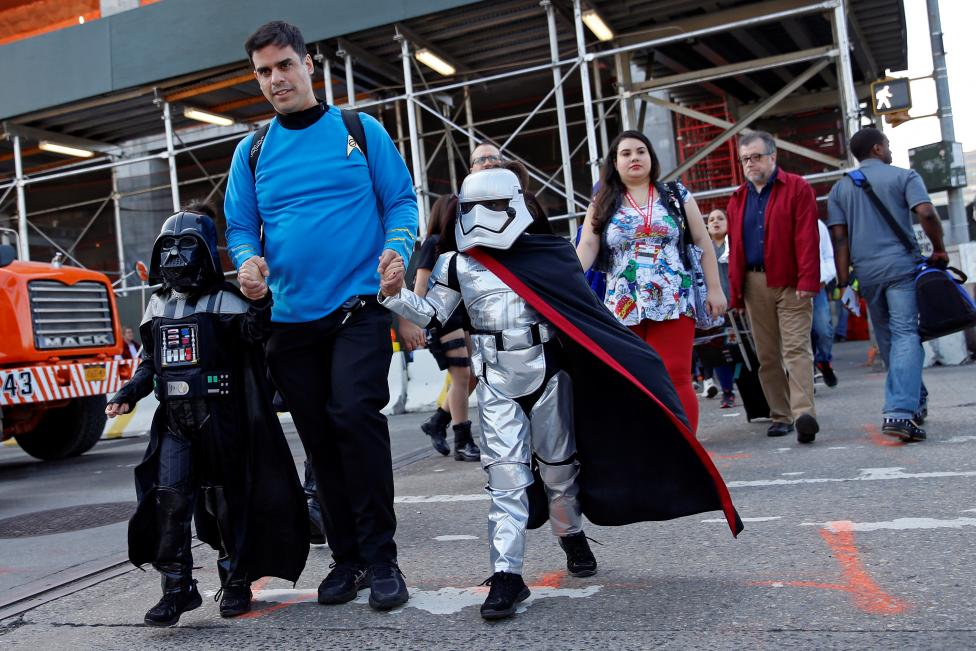 A man dressed in costume walks with children enroute to the New York Comic Con with other commuters in New York