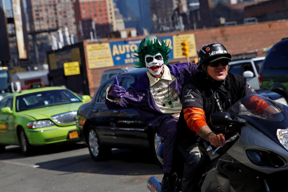 A man dressed in costume gives the thumbs up while riding on a motorcycle enroute to the New York Comic Con with other commuters in New York