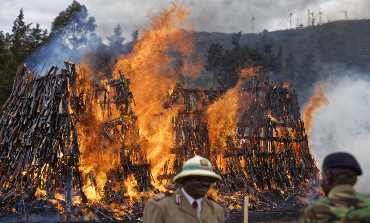 Kenyan police and officials watch as a pile of 5,250 illegal weapons are burned by Kenyan police in Ngong, near Nairobi, in Kenya Tuesday, Nov. 15, 2016. The weapons consisted of both confiscated and surrendered firearms that had been stockpiled over almost a decade and were destroyed by police as a message to the public to surrender others. (AP Photo/Ben Curtis)