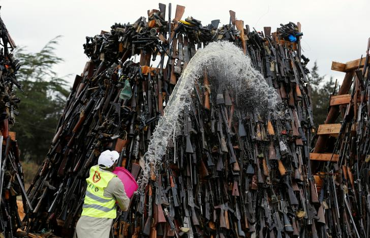 A worker pours fuel on an assortment of guns during a public burning of 5250 illicit firearms and small weapons, recovered during various security operations in Ngong hills near Kenya's capital Nairobi, November 15, 2016. REUTERS/Thomas Mukoya