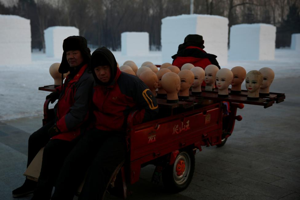 Workers transport heads of models as they prepare to sell hats at the festival. REUTERS/Aly Song