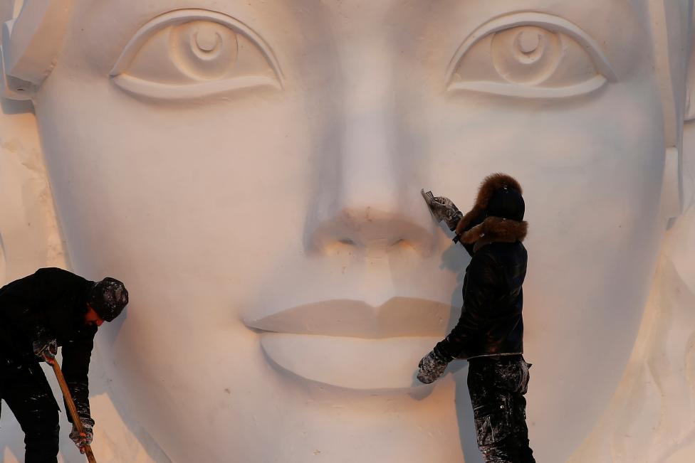 Artists prepare a snow sculpture. REUTERS/Aly Song