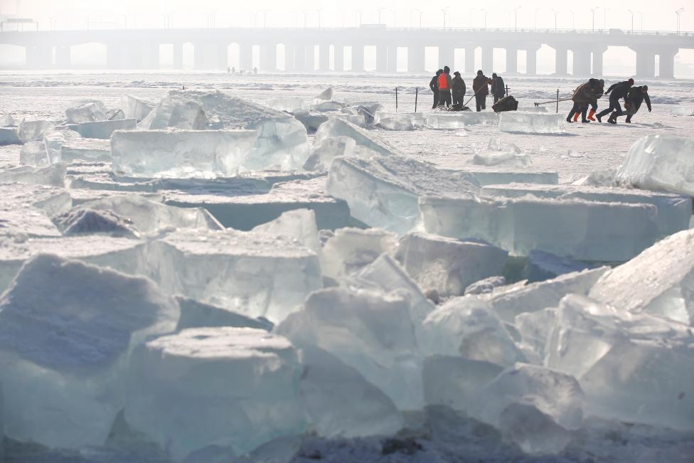 Workers pull a giant ice cube out of the frozen Songhua River as they extract ice to make sculptures. REUTERS/Aly Song