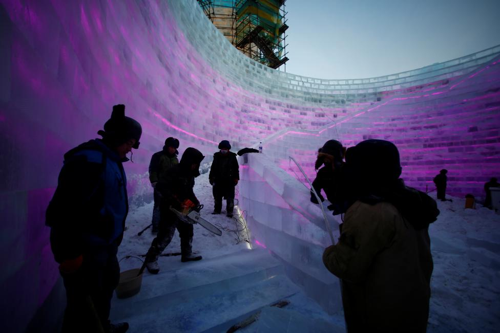 Artists and workers prepare an ice sculpture. REUTERS/Aly Song