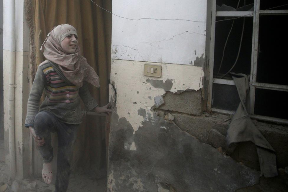 An injured girl reacts at a site hit by an airstrike in the rebel-held Douma neighbourhood of Damascus