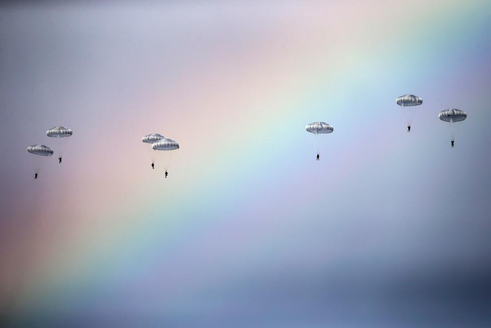 "Russian paratroopers jump past rainbow from an IL-76 transport plane during a joint Serbian-Russian military training exercise ""Slavic Brotherhood"" in the town of Kovin"