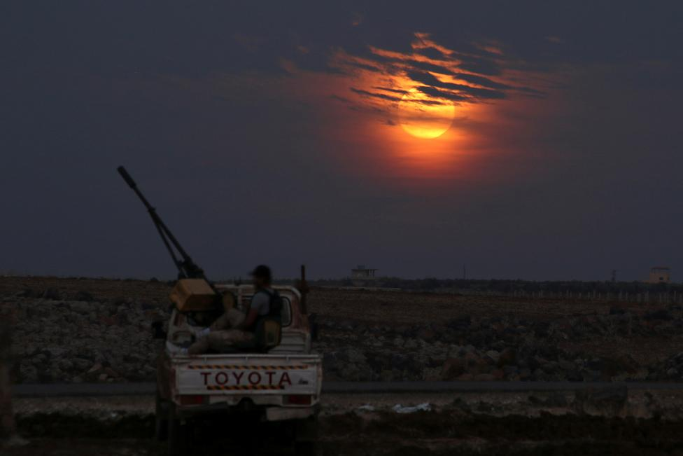A Free Syrian army fighter sits on a pick-up truck mounted with a weapon, as the supermoon partly covered by clouds is seen in the background, in the west of the rebel-held town of Dael