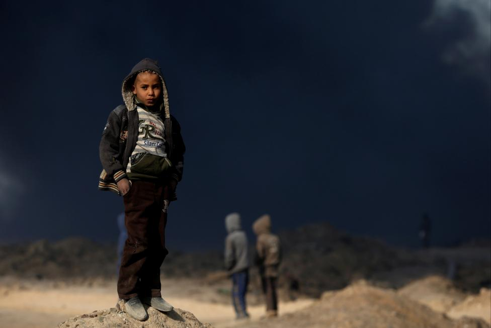 A boy stands in front of oilfields burned by Islamic State fighters in Qayyara