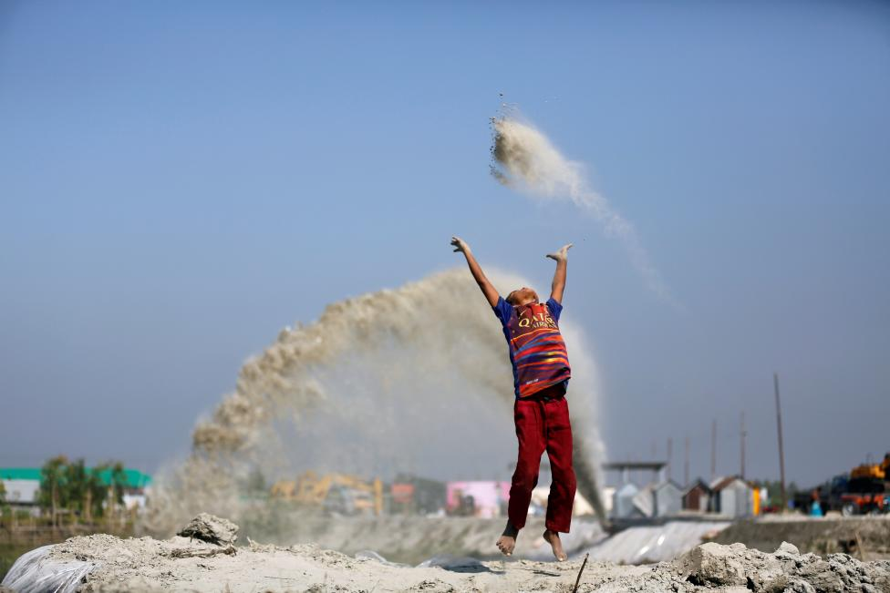 A boy plays with sand as his mother works in a nearby restaurant on the outskirt of Dhaka