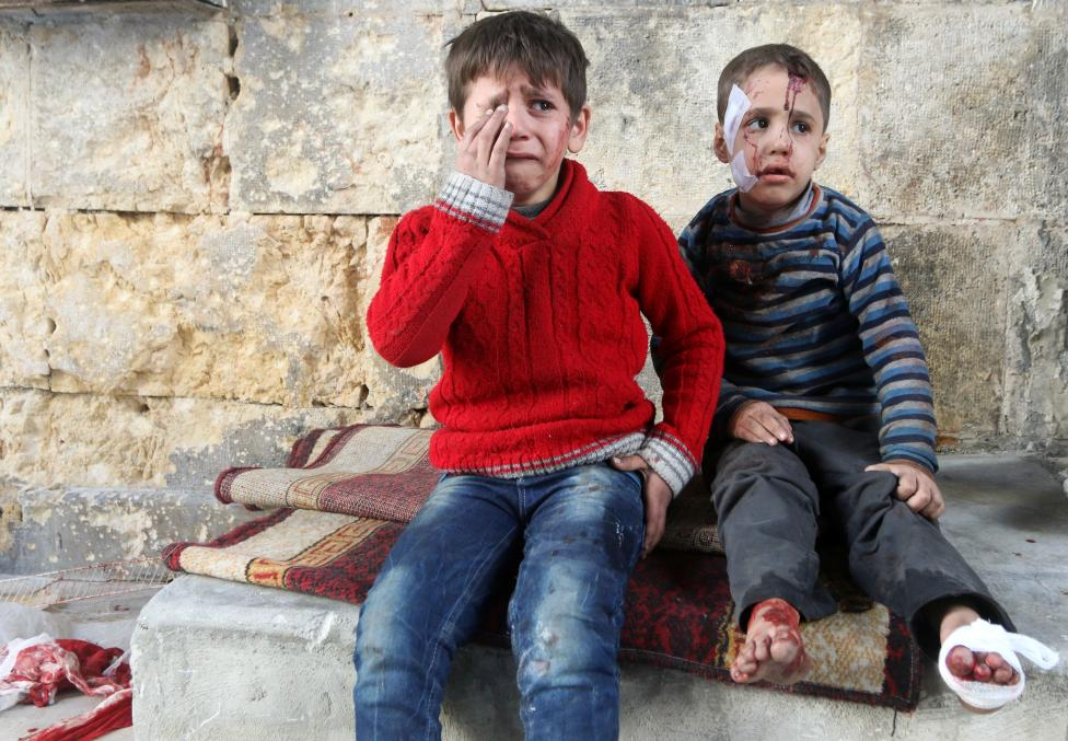 Injured boys react at a field hospital after airstrikes on the rebel held areas of Aleppo