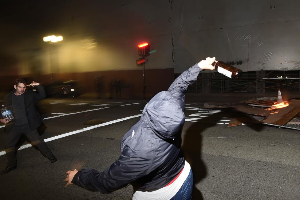 A protester throws a bottle at police officers following the election of Republican Donald Trump as President of the United States in Oakland, California