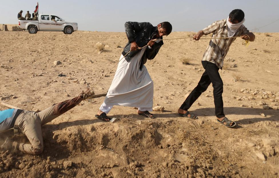 Men pull with a rope the body of an Islamic State fighter before burying him near Karamah
