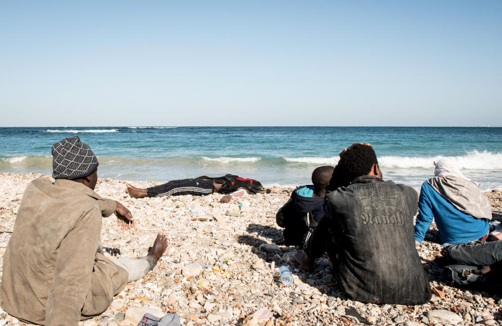 The dead body of Migrant is seen as other surviving migrants, who were on a boat which capsized on Wednesday, sit on a beach after policemen arrested them in Tripoli